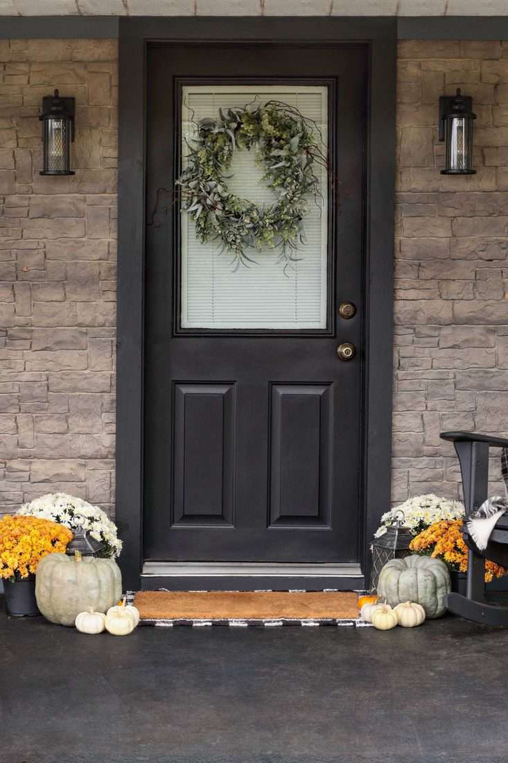 Brick front walls and dark wooden door with wreath made with leaves and white pumpkins
