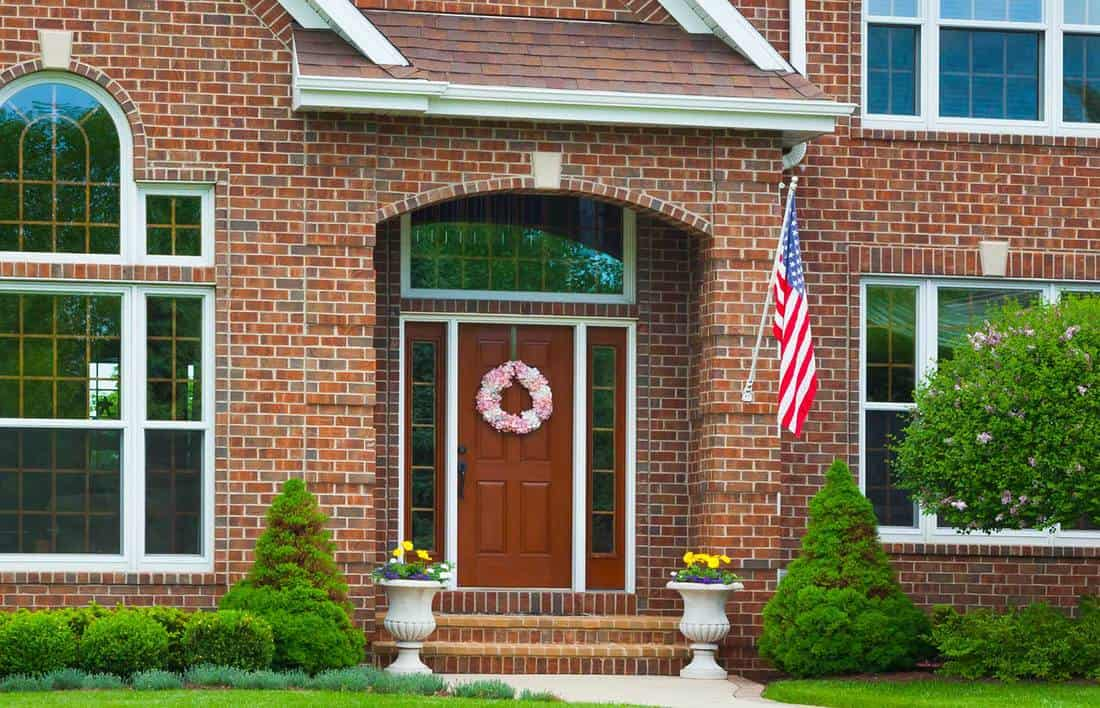 Brick home with american flag and wooden door