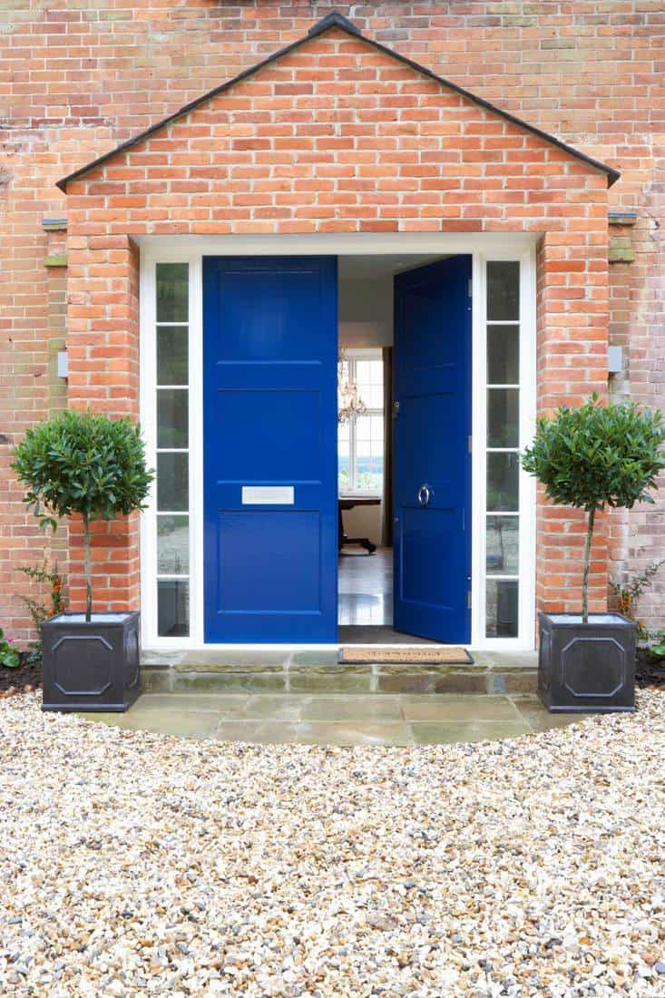 Brick themed porch with blue door and white and brown pebble-path