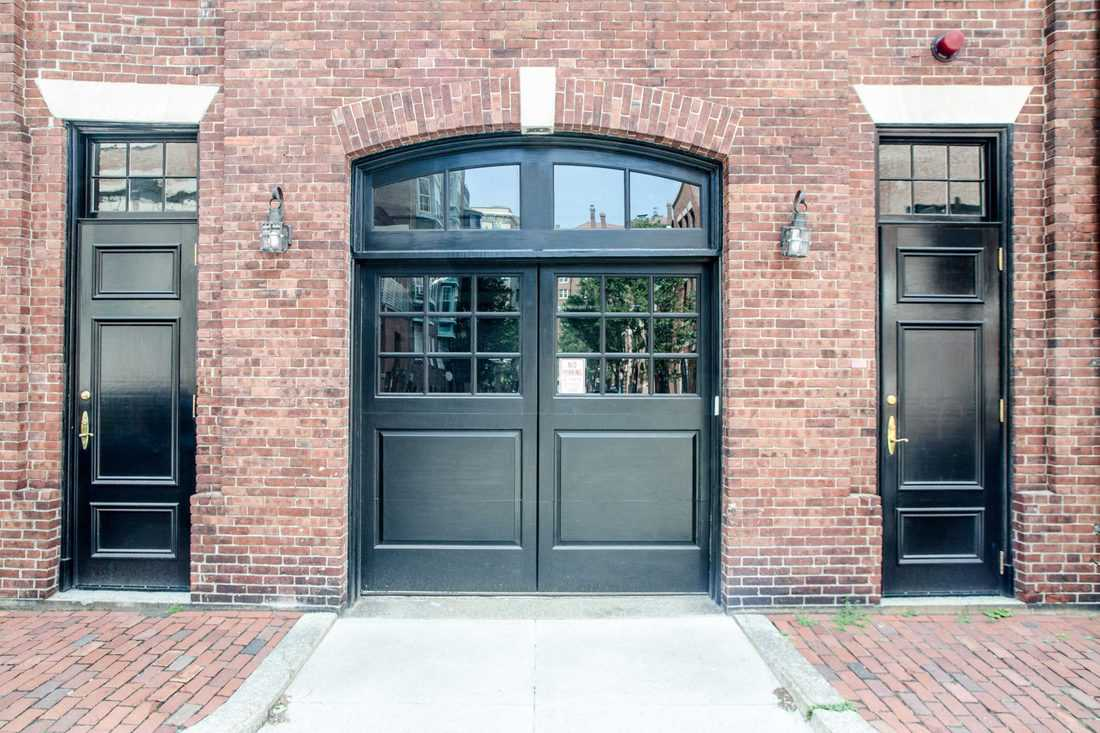 Brick walled facade with black double door with two single doors at side