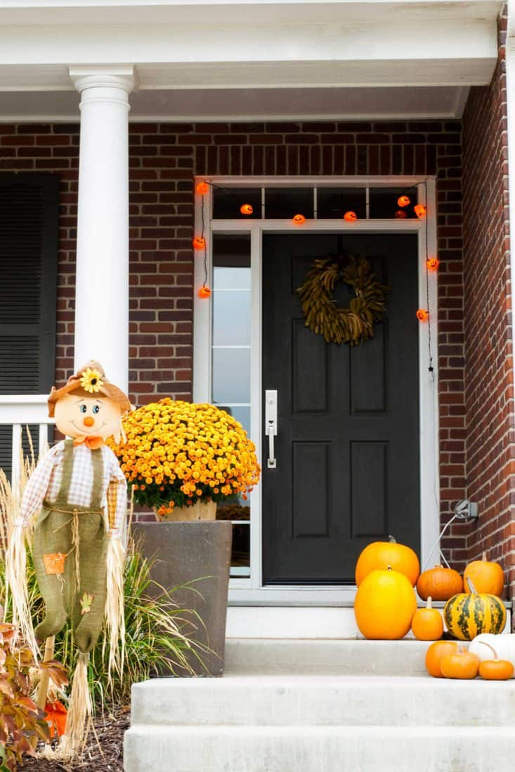 Brick walls with black door and pumpkins at stairs with friendly looking scare crow