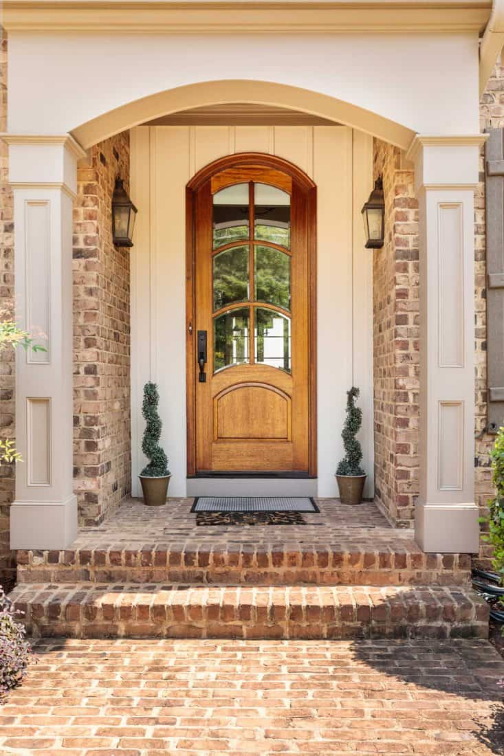 Brown arched door with arched with arched window and white framing and brick themed porch