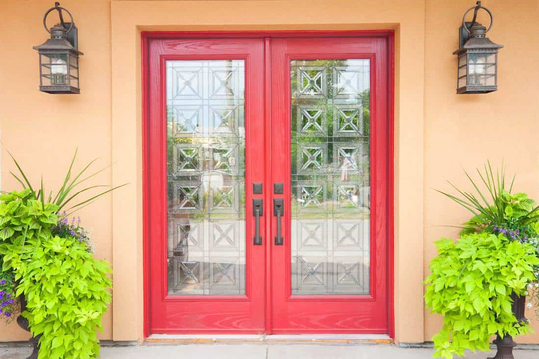 Brown colored porch with red french door with huge windows
