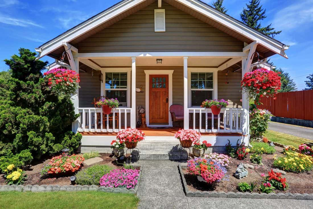 Brown door at typical porch design with garden in front