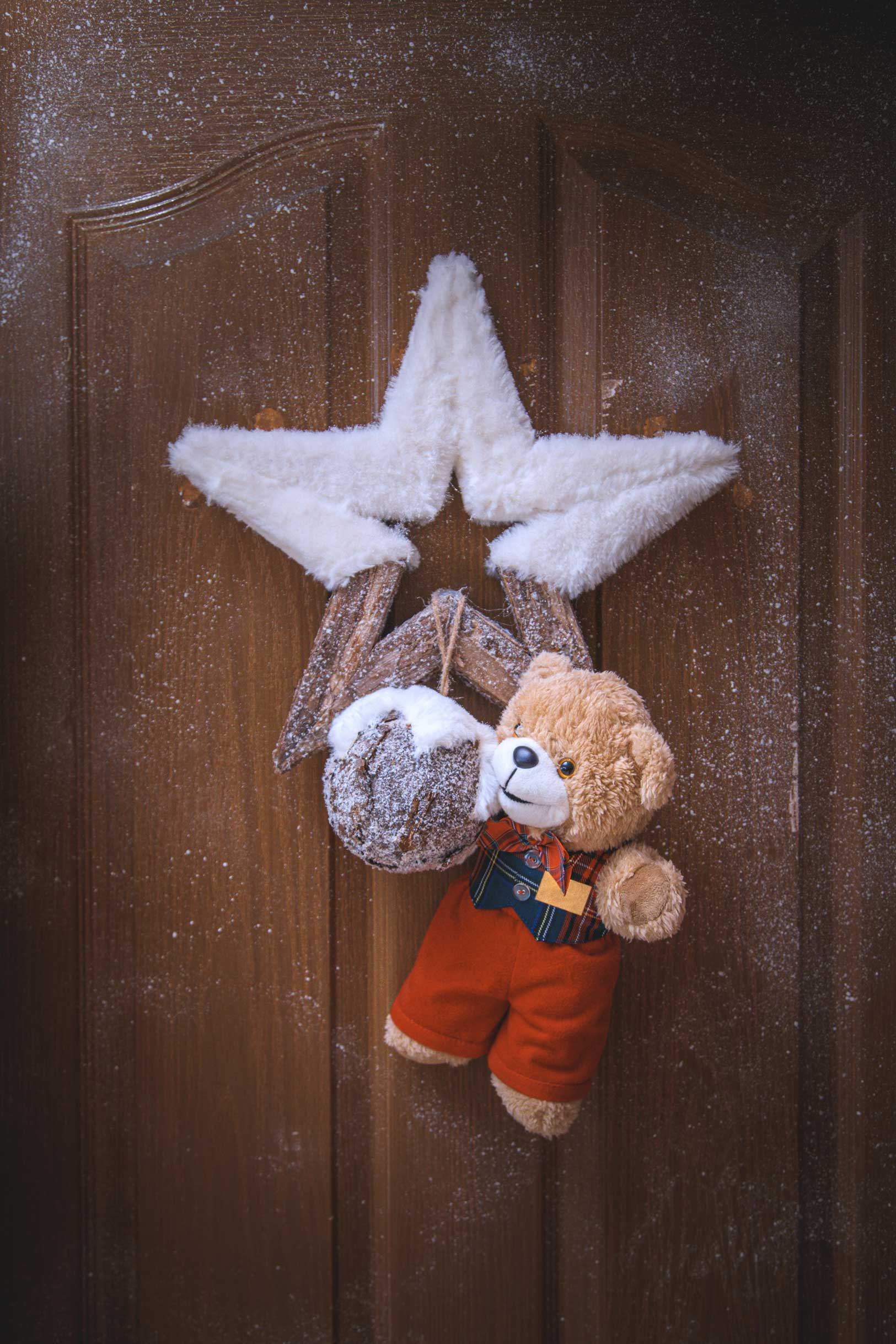 Brown door with wooden star coated with half white cover and hanging teddy bear