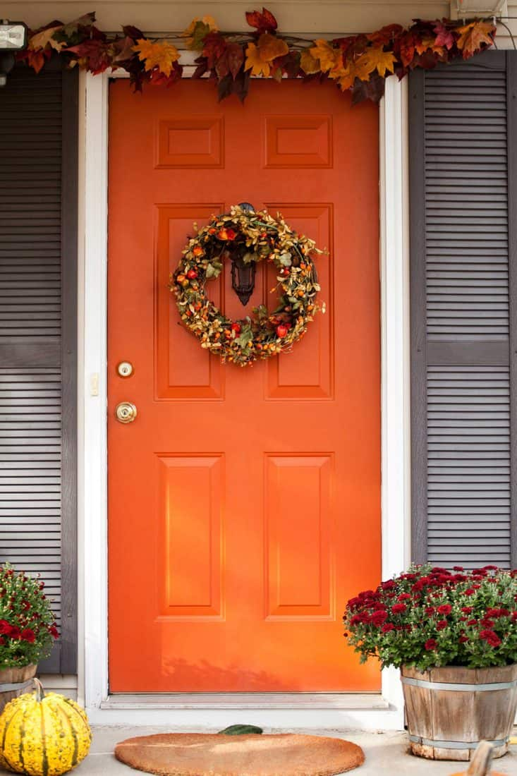 Brown door with wreath attached at door and hanging leaves at top
