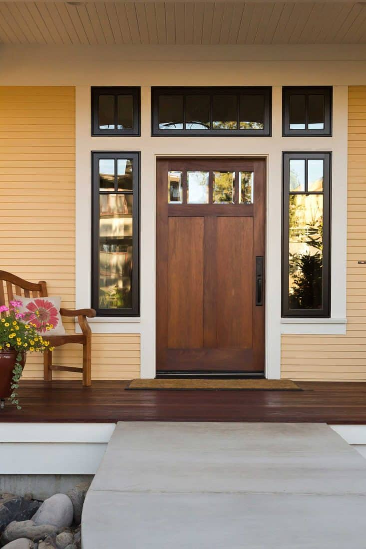 Brown laminated door with white colored framing and windows at sidings