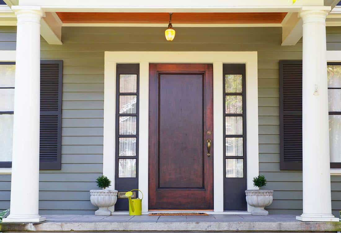 Brown stained front door on a home with bordering window and a pillared porch