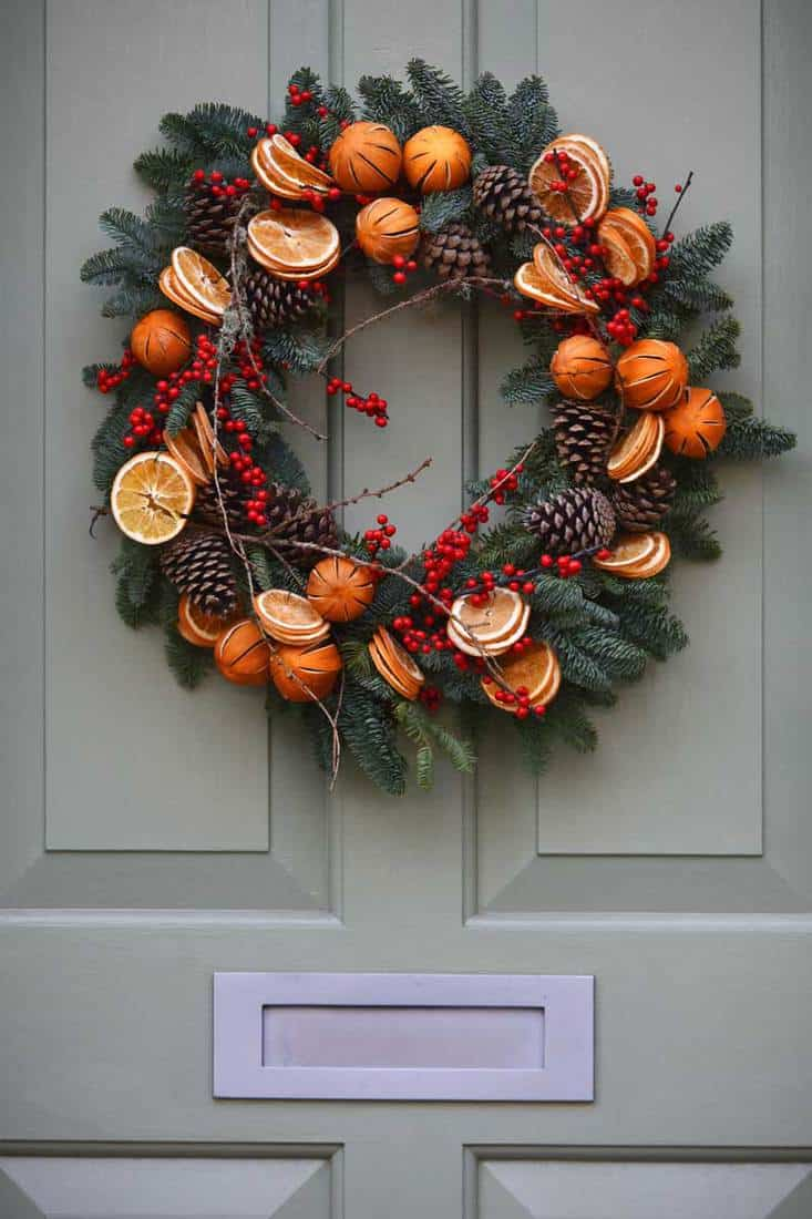 Christmas wreath attached with sliced oranges and red decorative berries for front door decoration