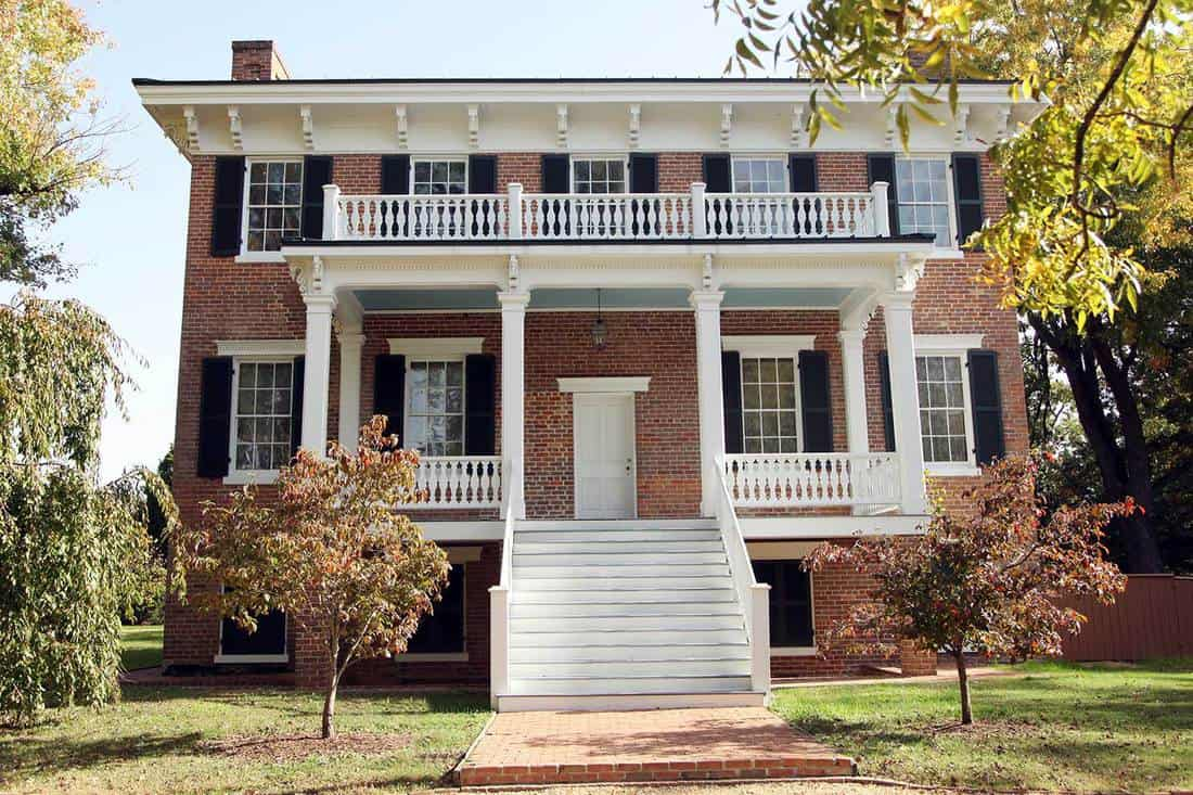 Colonial and greek revival style home with red brick walls, white door and stairway