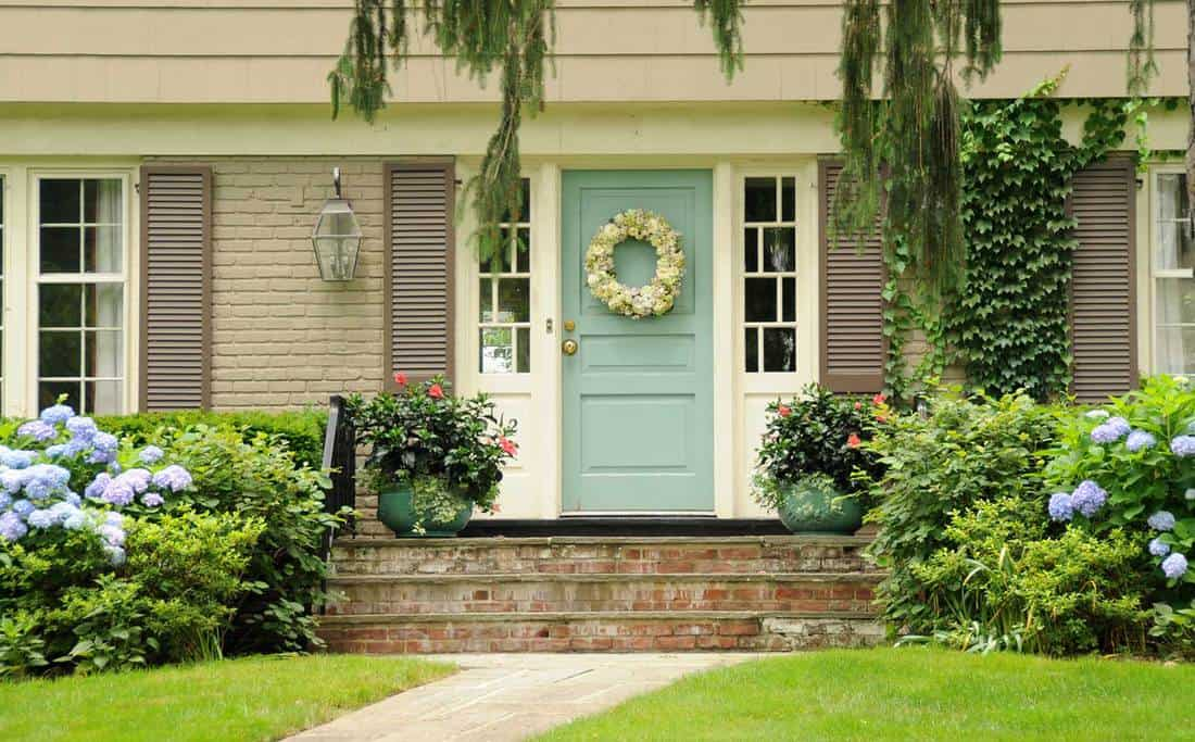 Colonial home with green door and lush greenery