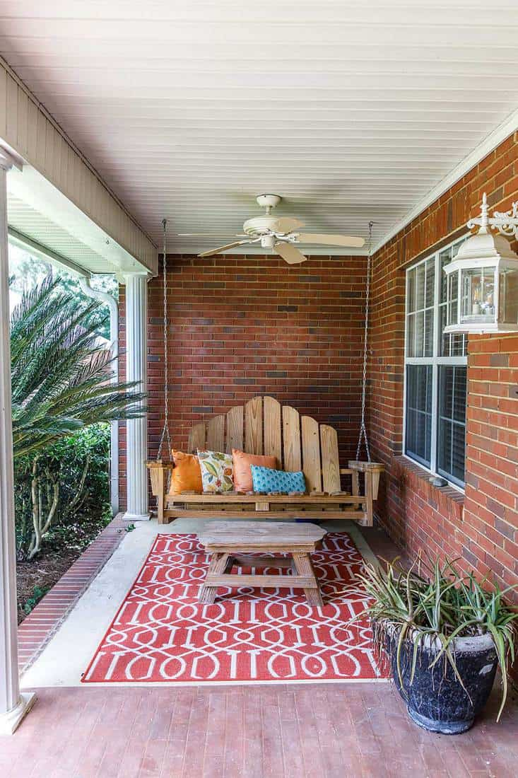 Colorful and modern boho outdoor front porch decoration with seating and plants of a traditional house with red brick walls