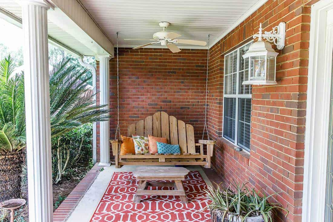 Colorful bohemian outdoor front porch decoration of a traditional house with red brick walls