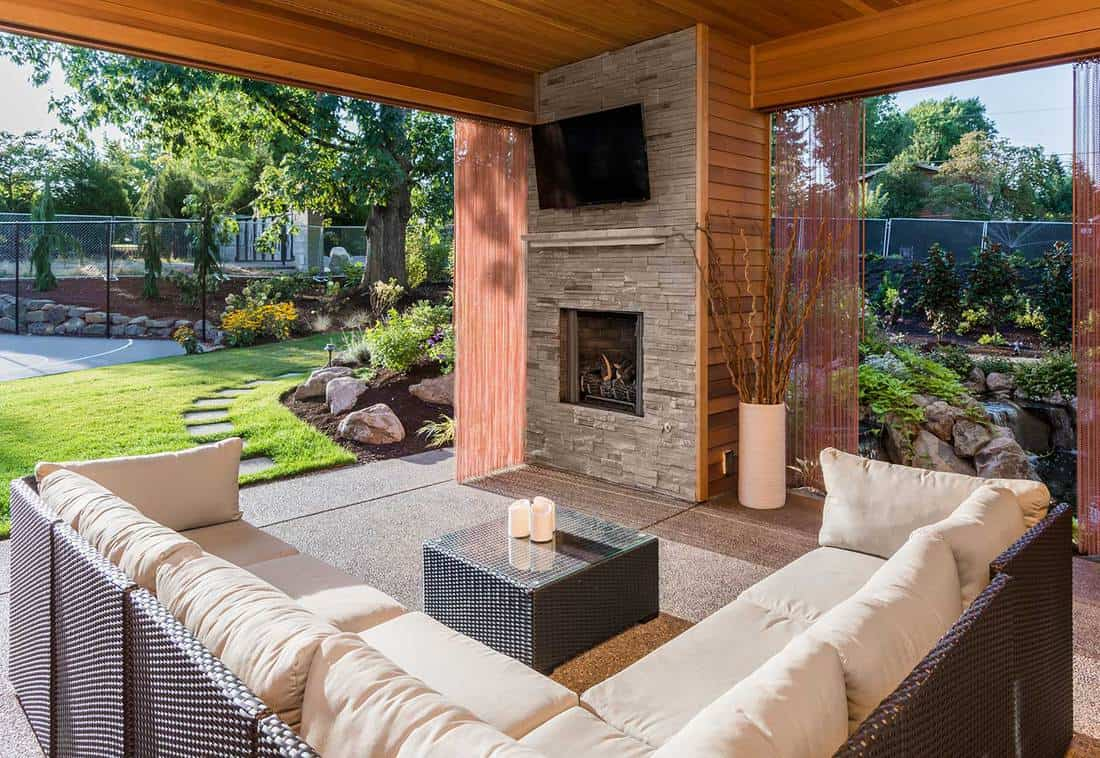 Covered patio exterior behind new luxury home with fireplace, tv, and couch, with view of lush green grass and landscaping
