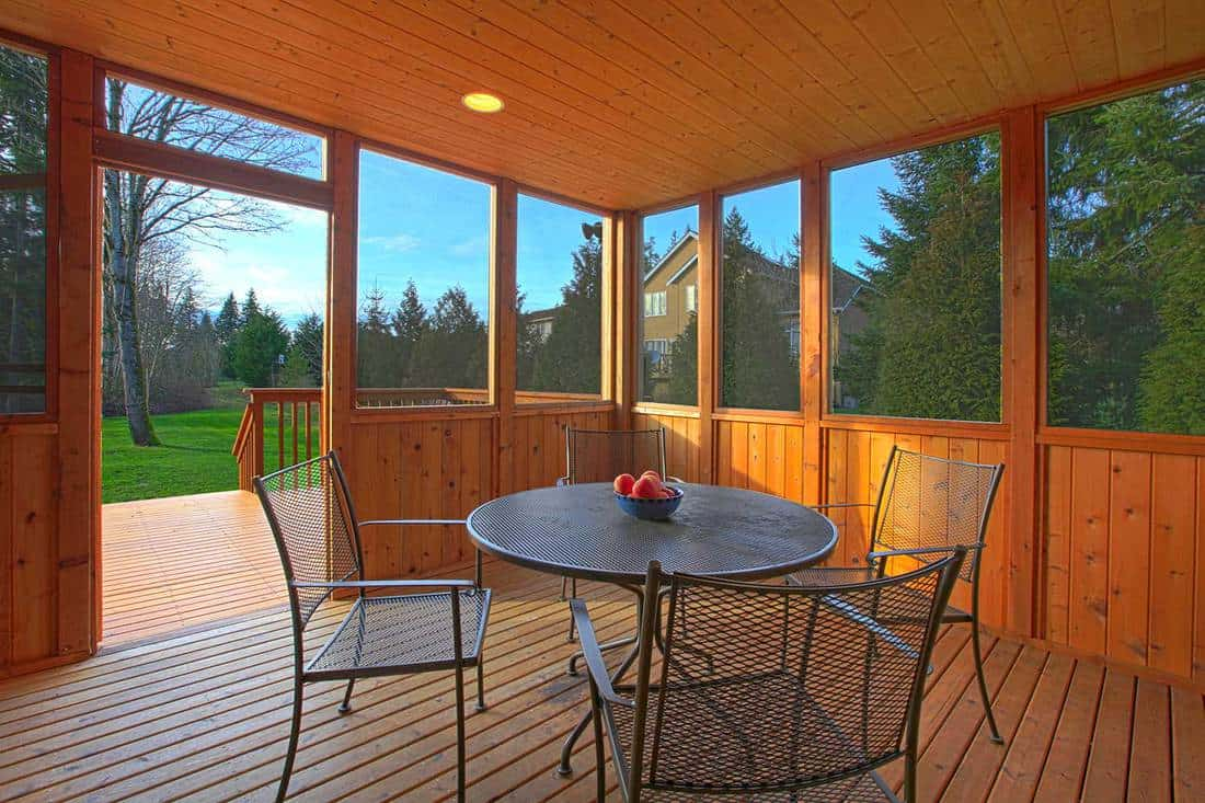 Covered screen porch on a wooden house with dining table and bowl of apples