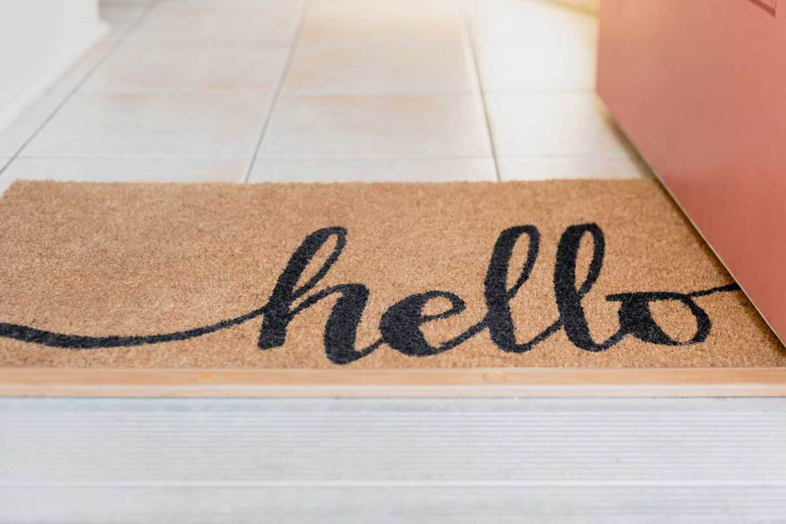 Cute rug with the word hello written in script at the entrance of a home welcoming guests