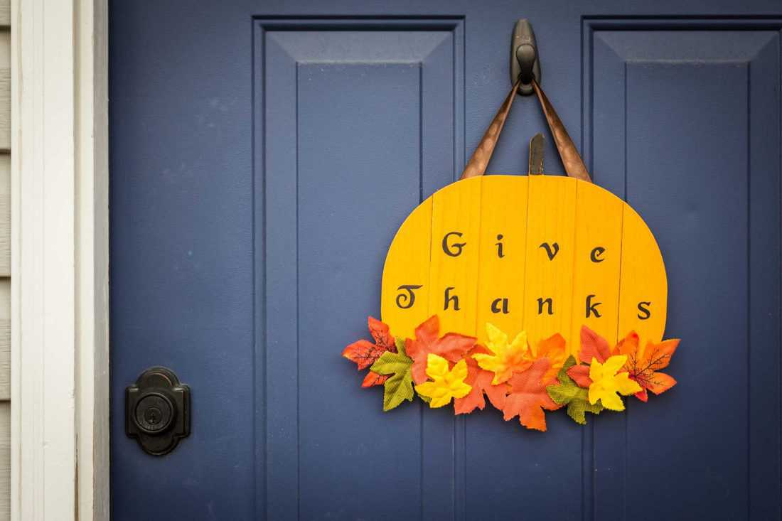 Dark blue door with give thanks pumpkin shaped sign with leaves at bottom