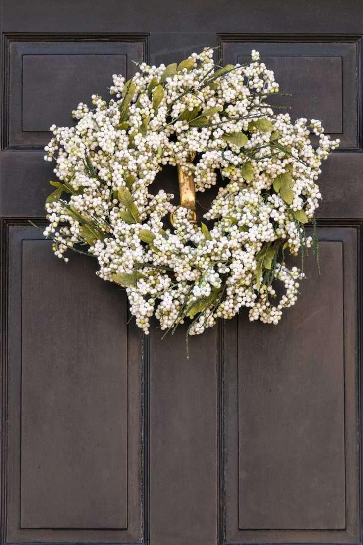 Dark brown door with flower designed wreath for front door decoration