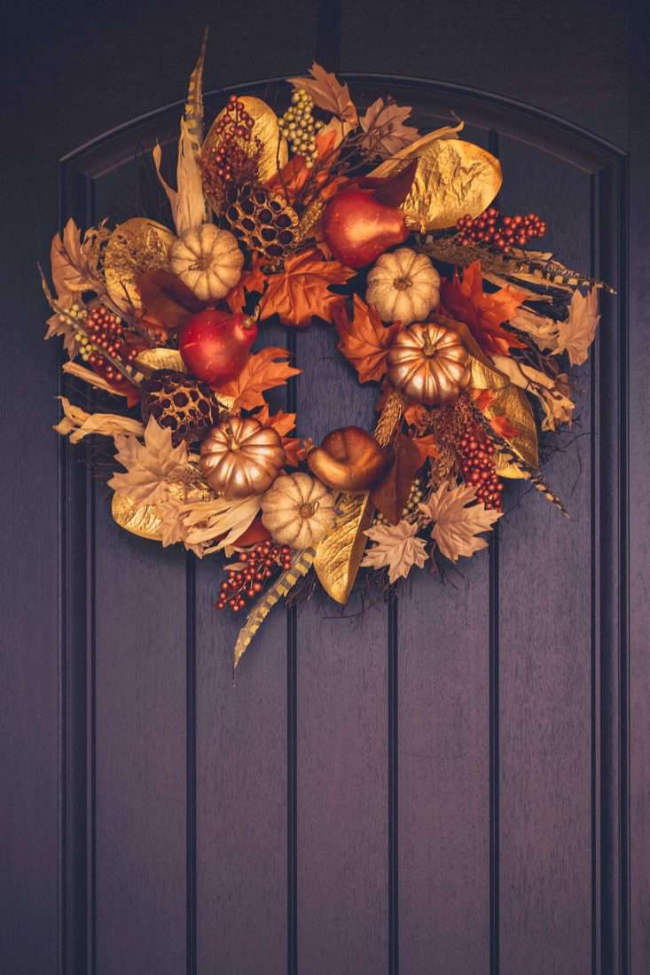 Dark purple door with wreath made with small pumpkin leaves and pine cones