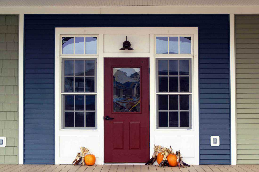 Dark red door with seamless window and white colored frame with windows