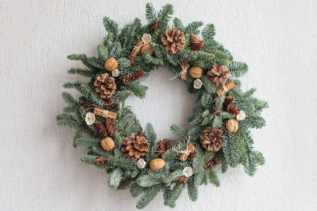 Decorative wreath with pine cones, acorns, and other decorative item for front door decoration