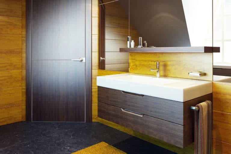 Rustic themed bathroom with dark yellow painted walls and brown vanity with white ceramic top