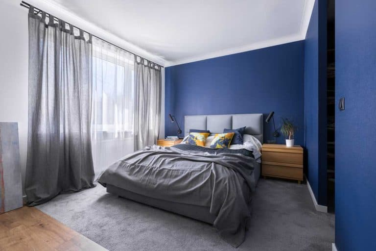 Blue walled bedroom with grey beddings and grey curtains