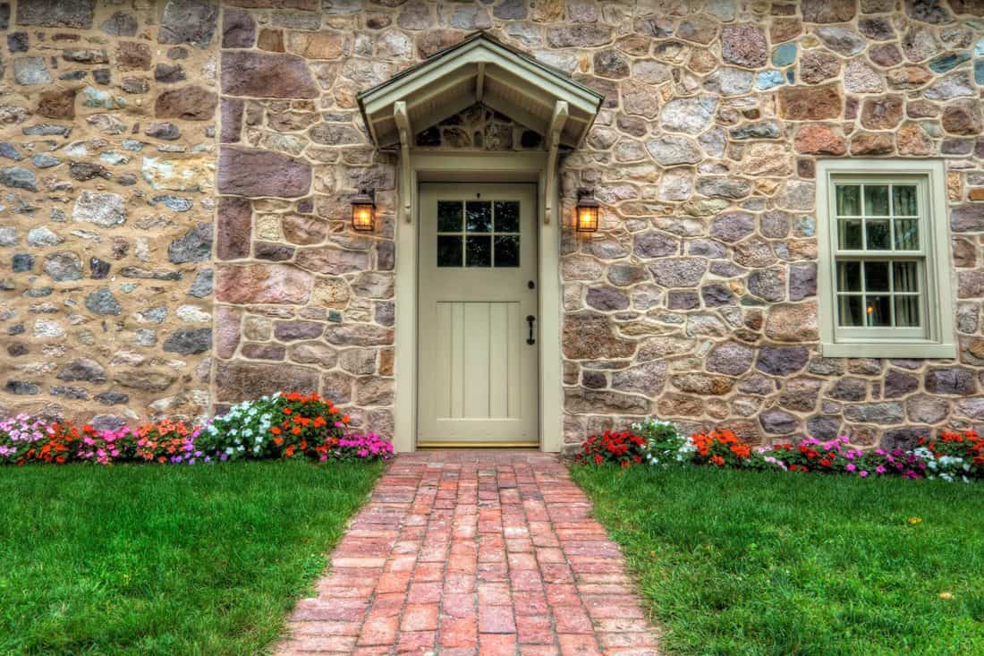 Dirty-white colored door at rock themed wall and brick pathway