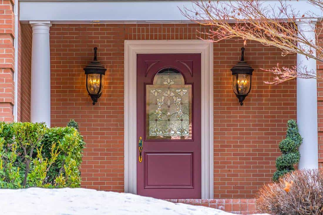 Entrance of a home with a beautiful red front door, exterior red brick wall and snowy yard
