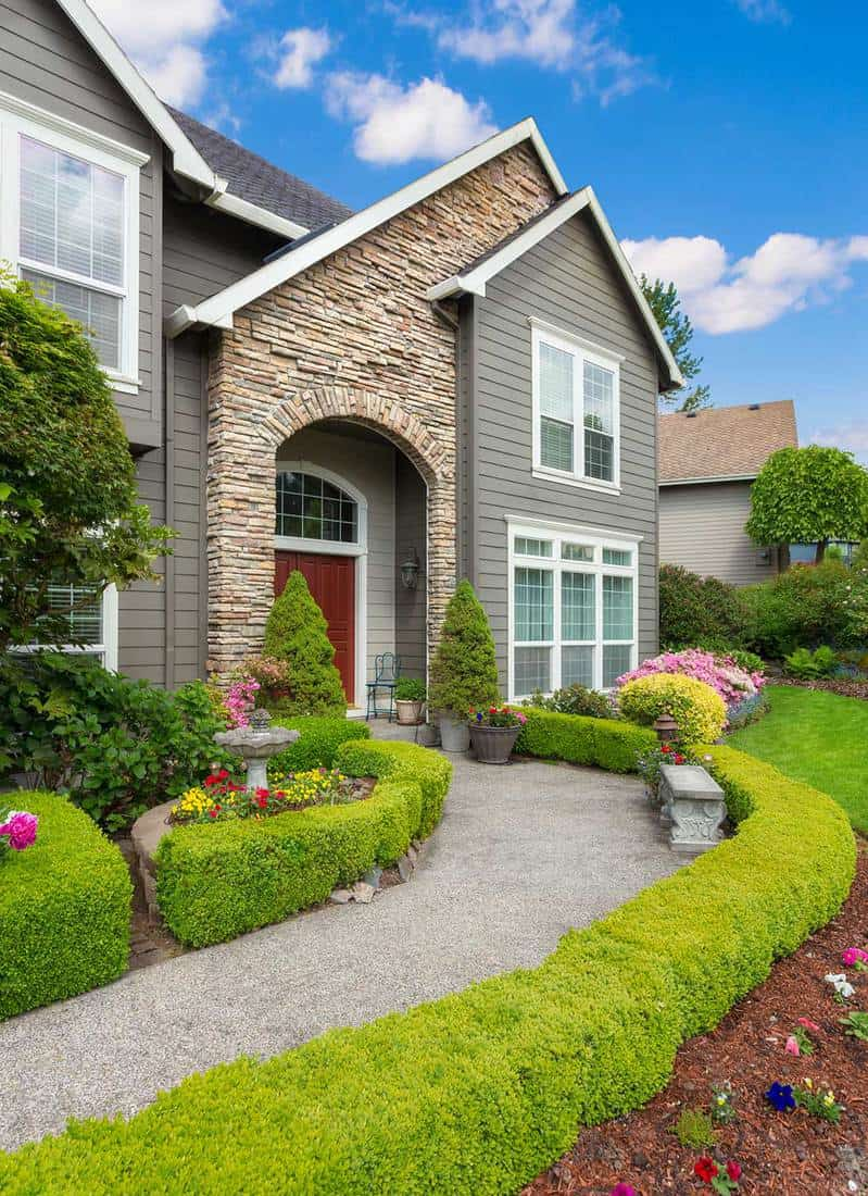 Facade of a beautiful home with walkway and manicured lawn