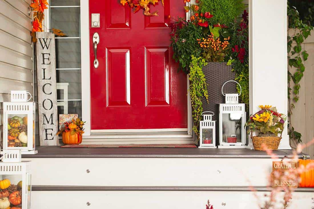 Farmhouse front porch with red front door, pumpkins, flowers and decorations