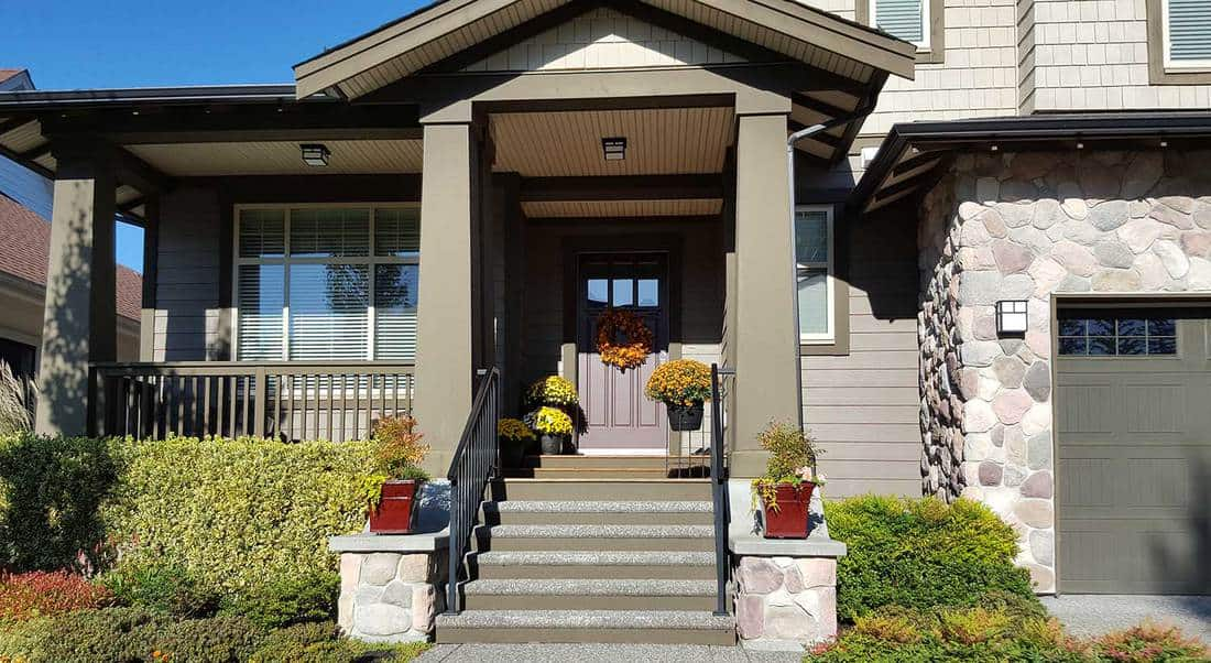 Front entrance of modern shingle and stone style home with autumn flowers and arrangements on stairs, porch and door