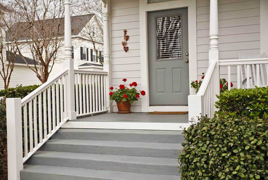 Front porch and stairway of a traditional American home with pot of geraniums