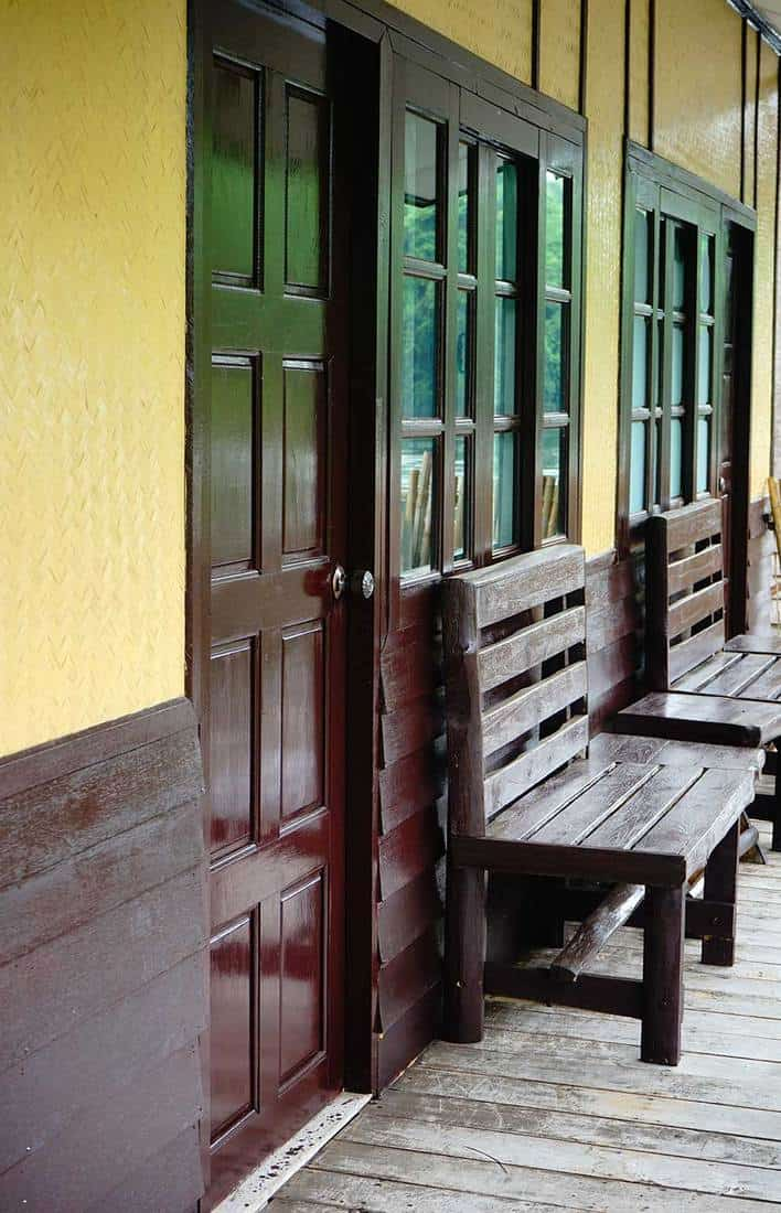 Front porch of a cabin home with wooden door and 2 wooden chairs