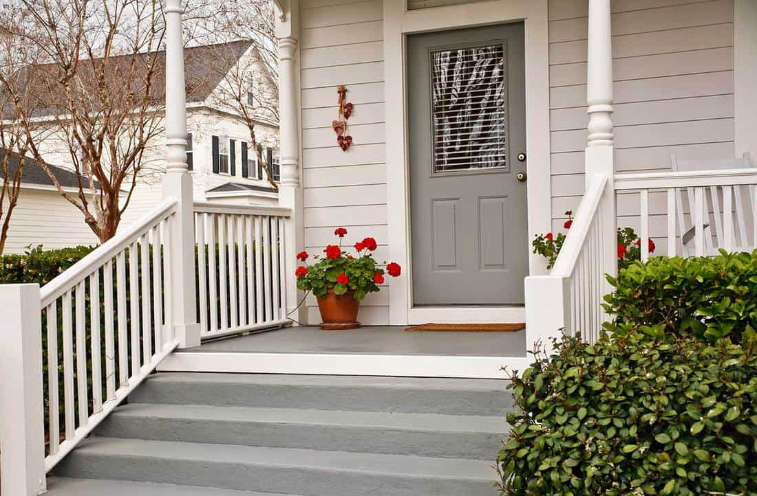 Front porch of a white house with gray door, stairway and pot of geraniums