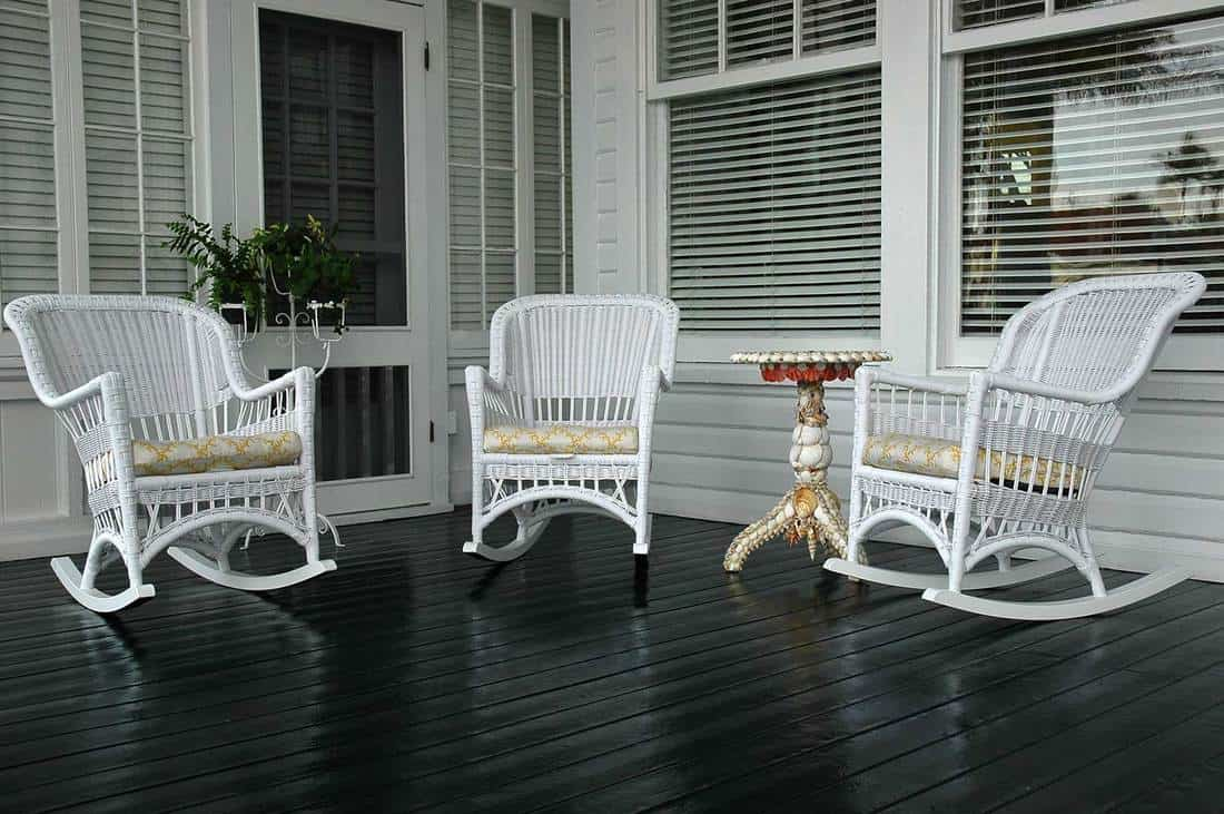 Front porch of a wooden house with glass windows and 3 white rocking chairs