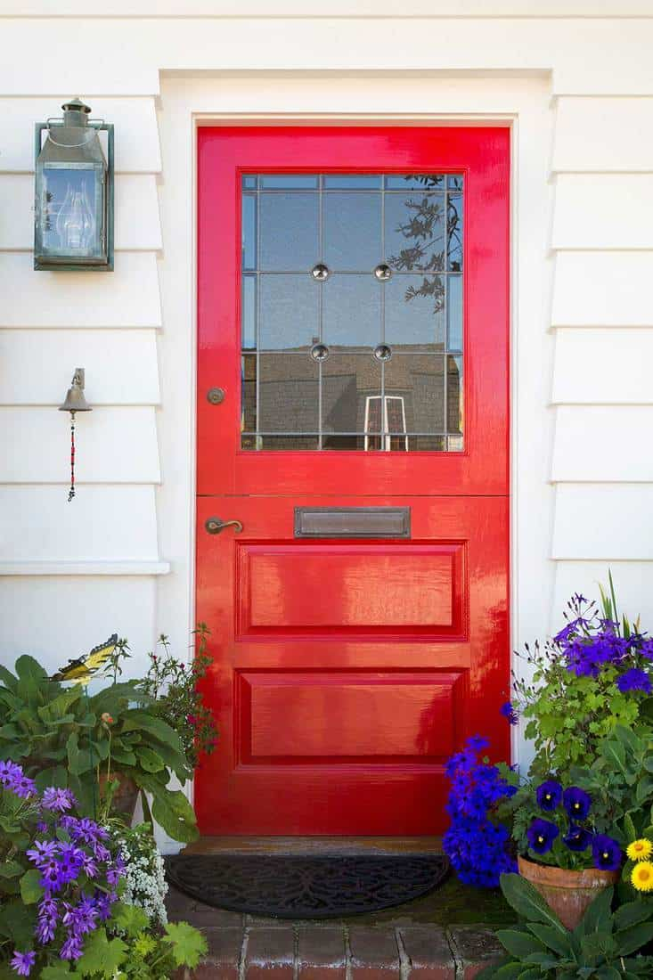 Full vertical view of a red front door of a white home with mail slot, door bell and plants