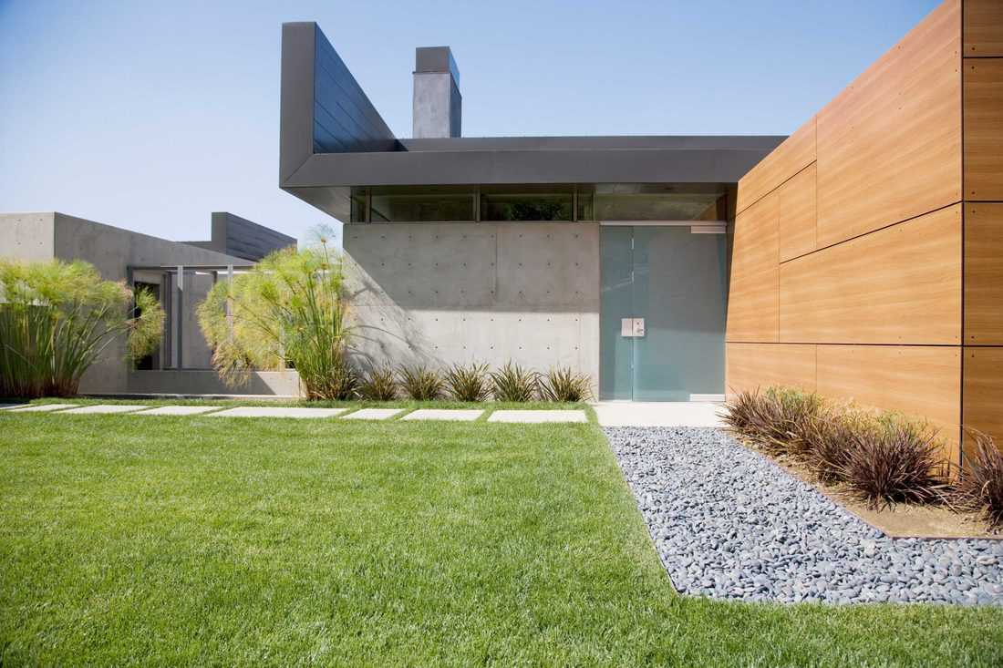 Glass pivot front door at modern facade with rectangular tile pathway and bermuda grass