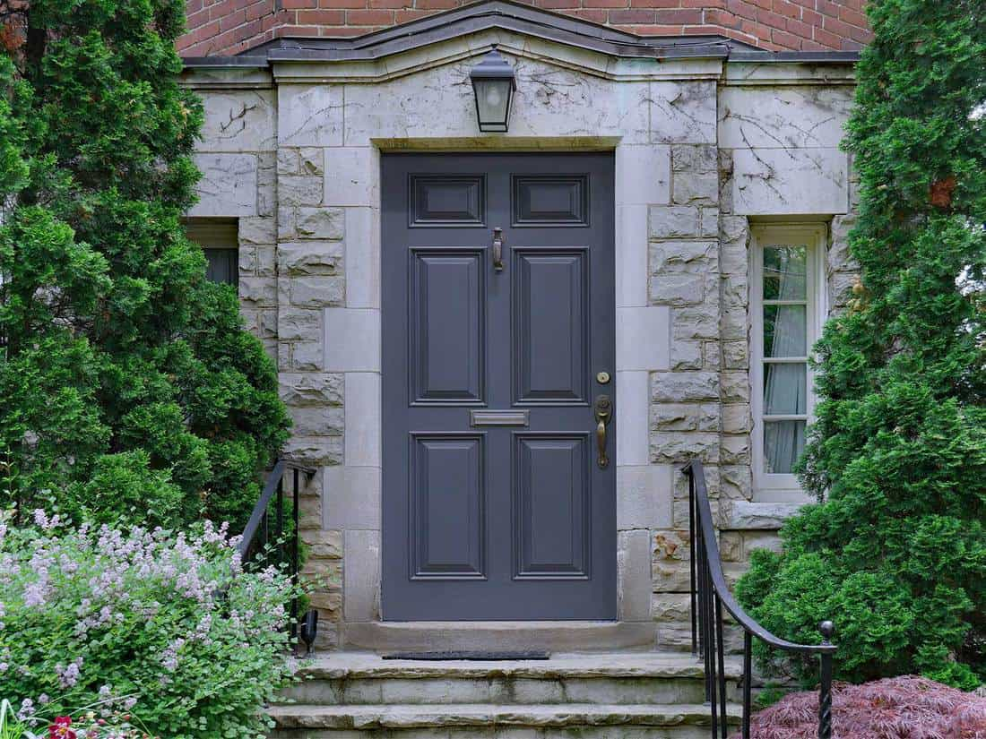 Gray front door of stone faced house surrounded by cedar bushes