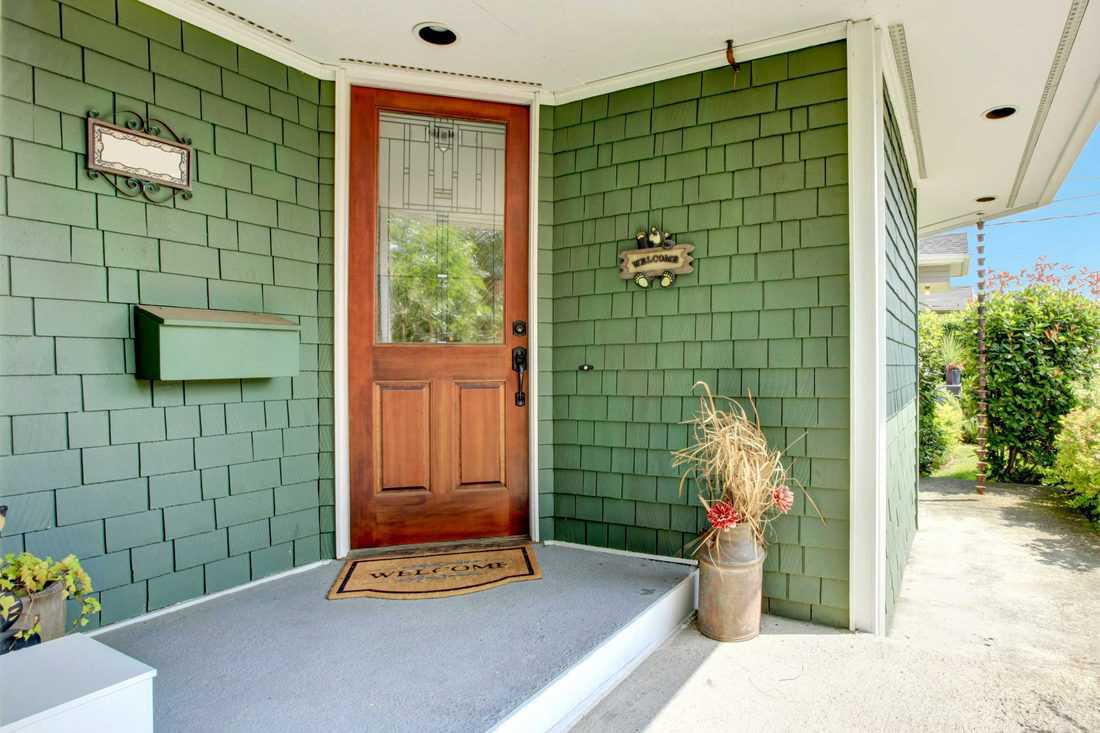 Green colored brick walls with brown colored door