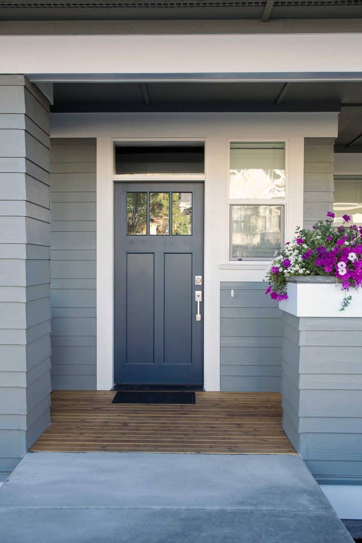 Grey themed porch with grey door and violet flowers on plant box