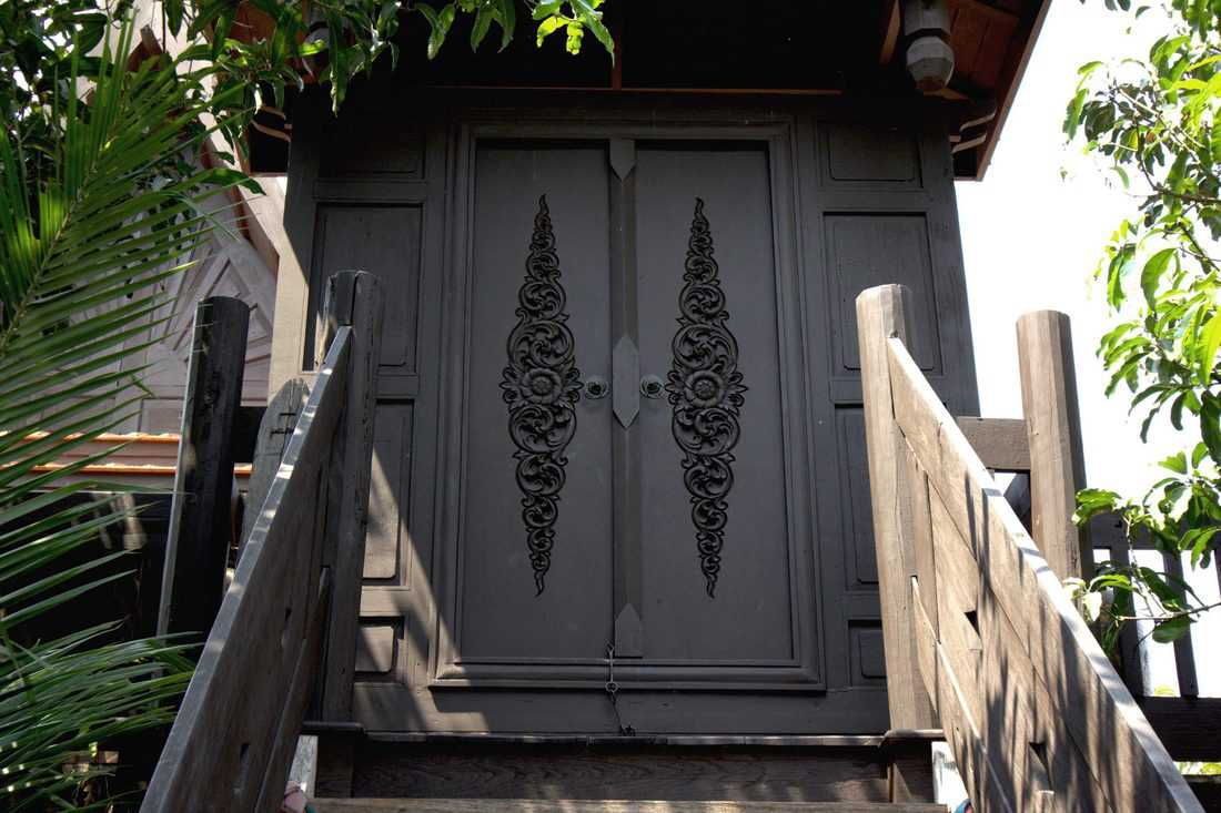 High stairway leading to black door with engraving