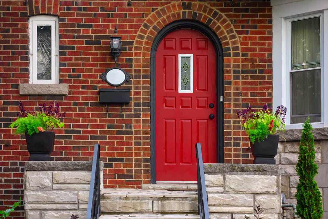 House facade with red front door and brick walls