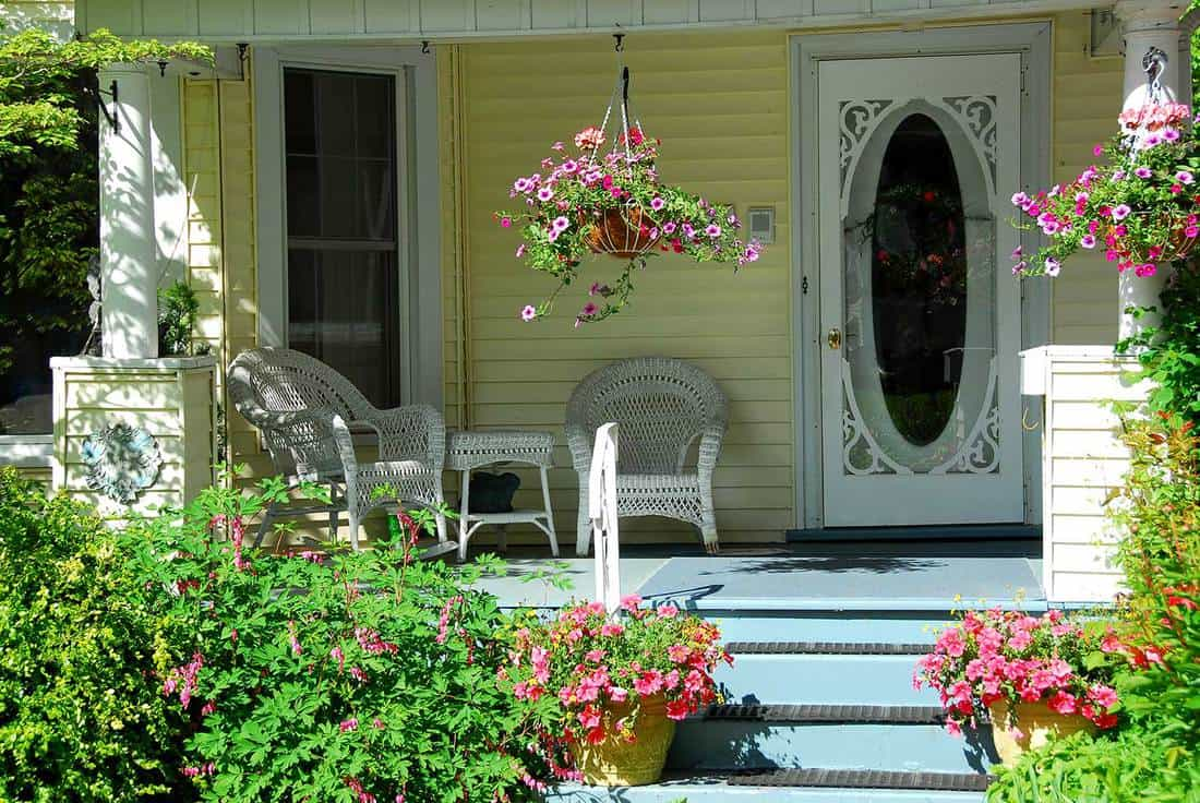 House porch with white door, plants and flowers