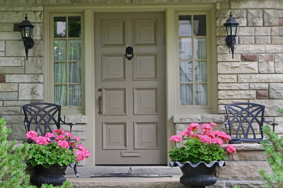 Light brown colored door with window sidings and pink flowers on pots
