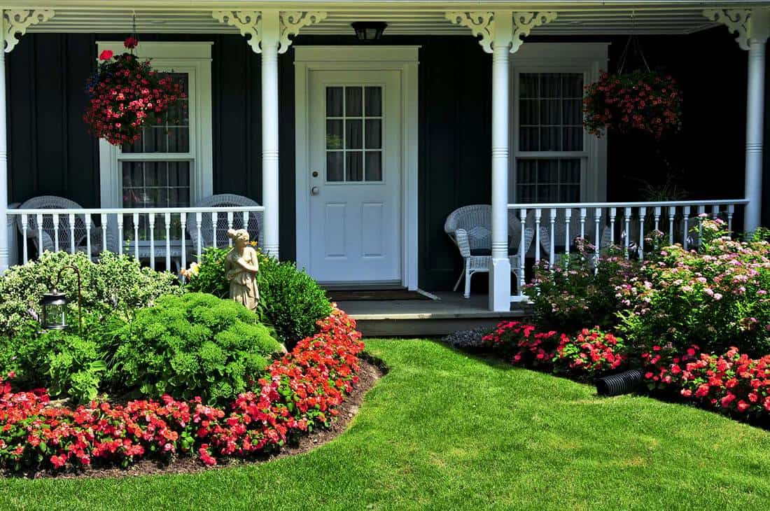 Landscaped front yard of a house with flowers and green lawn