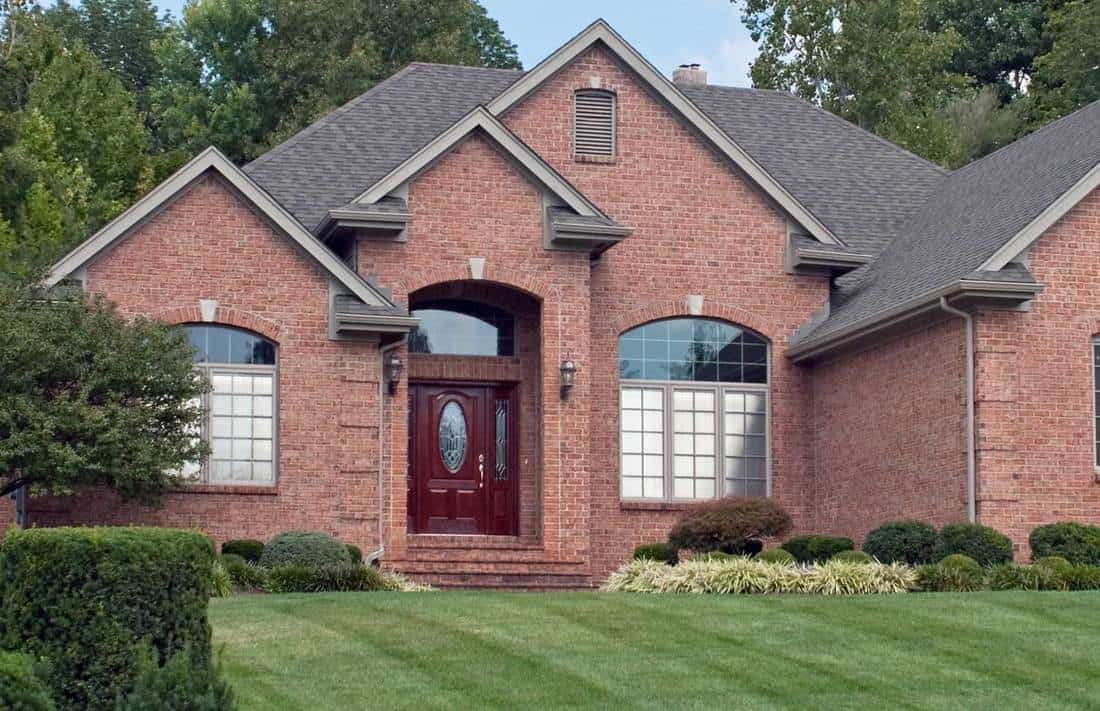 Large red brick home with red door in Midwest suburbs