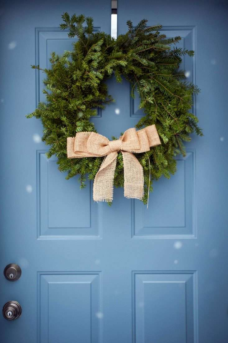 Leaf wreath attached in front of blue door with golden ribbon
