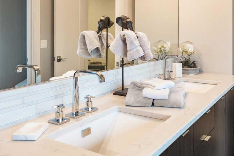Luxury bathroom with double sink vanity, towels and hand sanitizer