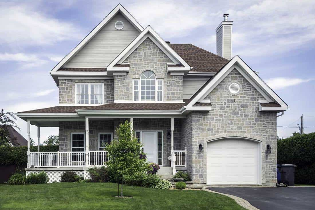 Luxury home with garage, white doors, stairway and front porch